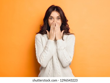 Portrait of amazed young woman over orange background