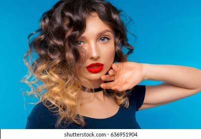Portrait of Amazing Beautiful Young Woman with Sexy Red Lips and Ombre Hair. Girl in Blue Top and Jeans. Isolated on Blue Background. Stylish hairstyle, Expressing True Emotions of Charming Model