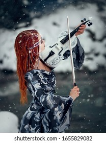 Portrait amazing cute slim young woman in chic fairy tale image in gray puffy dress and with crown on her head holds beautiful white violin and bow against background of white snow covered forest