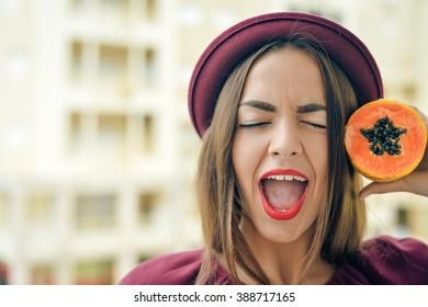 Portrait of amazing exciting beautiful elegant female wearing red felt hat holding half of papaya fruit next to her face, closeup