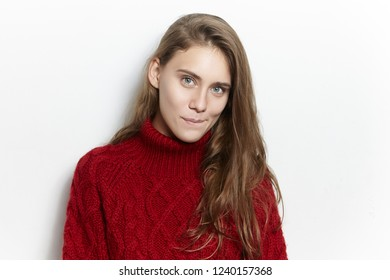 Portrait of amazing gorgeous young European woman with long loose hairstyle posing isolated in cozy marsala pullover, staring at camera with mysterious curious facial expression, biting lips