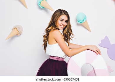 Portrait amazing stylish model with long brunette hair, in tulle purple skirt holding big lollipop isolated on white background with ice creams. Pretty woman smiling to camera surround sweets