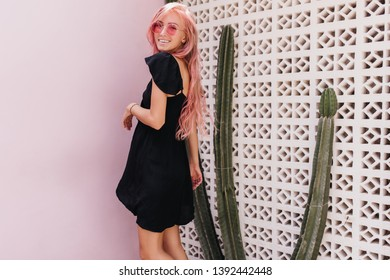 Portrait of amazing woman in black dress looking over shoulder with cute sincere smile. Photo of glad female model with pink hair standing near exotic cactus.