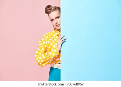 Portrait of amazing young serious woman model wearing yellow blouse with white polka-dot, blue skirt in pin-up style, hiding behind light blue wall in studio with blue and pink background
