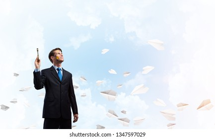 Portrait of ambitious and young business man in suit holding paintbrush in hand while standing against blue cloudy skyscape view with flying paper planes on background.
