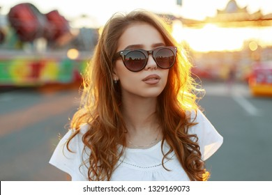 Portrait of American cute young redhead hipster with sexy lips in fashionable sunglasses in a stylish white t-shirt in an amusement park on a background of bright orange summer sunset. Pretty girl.