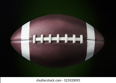 portrait of a american football ball in dark background / american football ball
