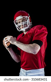 Portrait of american football player being about to throw football against black background