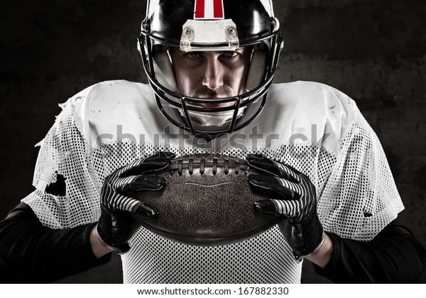 Portrait of american football player holding a ball and looking at camera