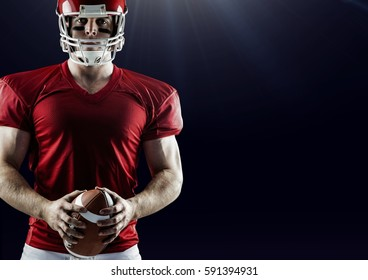Portrait of american football player standing with ball against black background