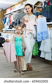 portrait of american glad woman and girl shopping kids apparel in clothes store