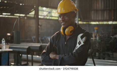 Portrait American industrial black young worker man smiling with yellow helmet in front machine, Engineer standing holding wrench tools and arms crossed at work in the industry factory.