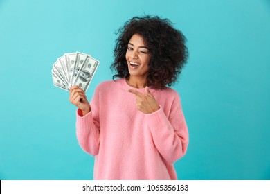 Portrait of american successful woman 20s with afro hairstyle holding lots of money dollar