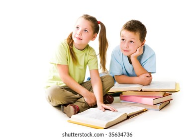 Portrait of amused pupils looking aside during reading books