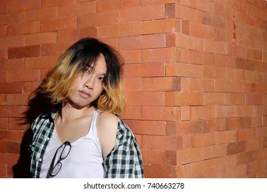 Portrait of androgynous beautiful young man as a beautiful woman on brick wall background.