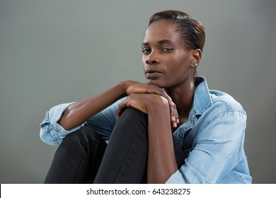 Portrait of androgynous man in denim shirt posing against grey background