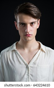 Portrait of androgynous man posing against grey background