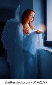 Portrait of an angel with a candle standing near the window.