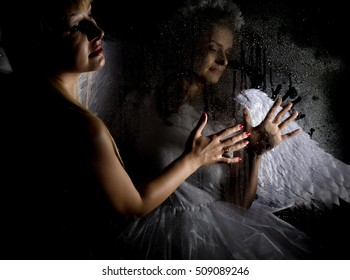 Portrait of angel and devil womans on a dark background, behind transparent glass covered by water drops