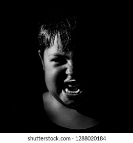 Portrait of anger young caucasian boy. Scary and agression concept. Black and white shot, low key lighting. Isolated on black.