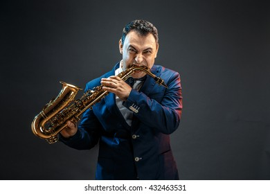 Portrait of angry adult man biting sax.Studio shot.Isolated.