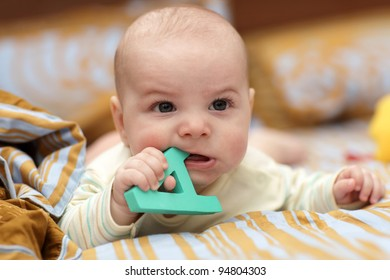 Portrait of angry baby with alphabet at home