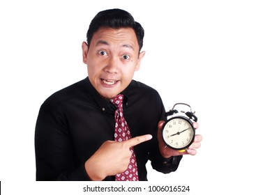 Portrait of angry businessman business manager boss showing alarm clock, mad of his too late employee