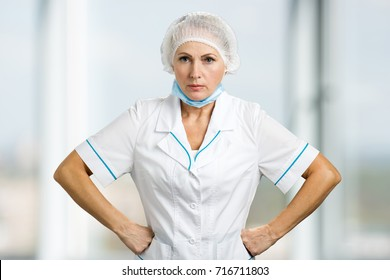 Portrait of angry female doctor. Frustrated mature female doctor keeping hands on hips.
