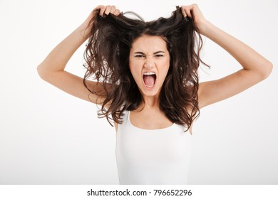 Portrait of an angry girl dressed in tank-top pulling her hair out and screaming isolated over white background