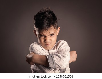 portrait of angry kid on gray background