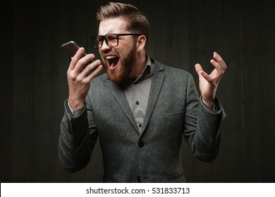 Portrait of an angry man in casual suit screaming at mobile phone isolated on the black wooden background