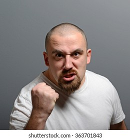 Portrait of a angry man holding fists against gray background
