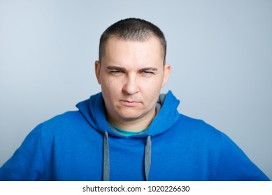 portrait of an angry man holding hands on his waist, wearing a blue hoodie, isolated on a gray background
