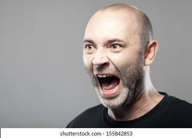 portrait of angry man sreaming isolated on gray background with copyspace