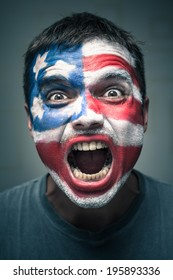 Portrait of angry man with USA flag painted on face.