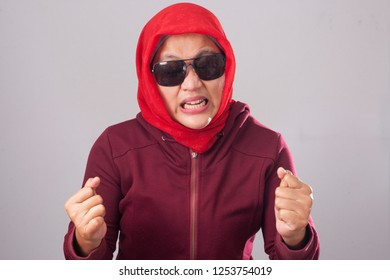 Portrait of angry muslim woman wearing black sunglasses in red suit and hijab shows mad insanity gesture