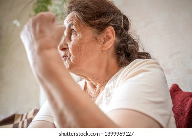 Portrait of an angry old woman showing fist