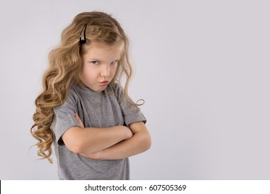 Portrait of angry and sad little girl isolated on white background. Children's emotions