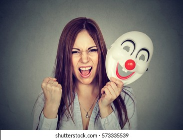 Portrait angry screaming woman taking off a clown mask expressing happiness isolated on gray wall background. Human emotions feelings