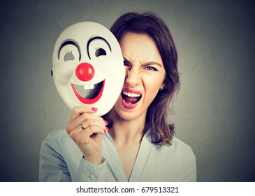 Portrait angry screaming woman taking off happy clown mask isolated on gray wall background. Negative human emotions feelings