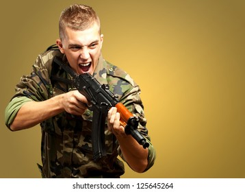 Portrait of an angry soldier aiming against a yellow background