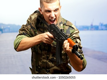 Portrait of an angry soldier aiming, outdoor