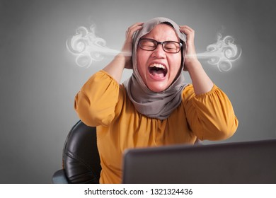 Portrait of angry stressed muslim businesswoman wearing hijab with mad insanity gesture