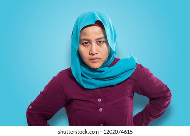 Portrait of angry sullen unhappy cynical muslim woman businesswoman with arms on hips against blue wall