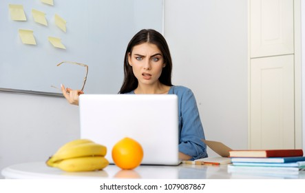 Portrait of angry, surprised and impressed woman with widened eyes and opened mouth, stunned because of something she sees on screen of computer. takes off her glasses from her face. Orange, bananas.