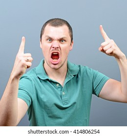 Portrait of a angry threatening man screaming against gray background