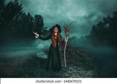 A portrait of an angry witch with a broodstick near the forest. Magic, dark force, spell.