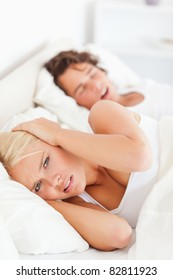 Portrait of an angry woman awaken by her boyfriend's snoring while looking at the camera