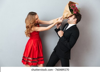 Portrait of an angry woman beating up a man with a flower bouquet over gray wall background
