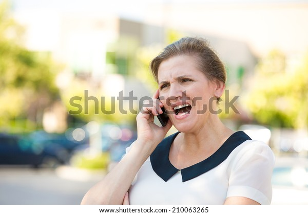 Portrait Angry Woman Screaming while Talking on mobile Phone, isolated outdoors parking lot background. Negative human emotions, facial expressions, feelings, attitude. Bad communication concept